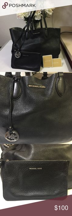 Michael Kors Reversible Bag Gently used MK reversible bag! Great condition as can be seen in the pictures and comes with an attached wallet / pouch. The inside has slots to hold cards. On the inside of the bag, it's silver and has a few black and blue marks. Not too noticeable but are there (picture 8). Michael Kors Bags