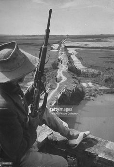 French soldier guarding against Communist infiltration looking across border into Red China.