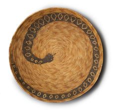 MISSION POLYCHROME PICTORIAL COILED TRAY finely woven with black-dyed juncus over grass, with an encircling rattle snake design, a series of graduated diamonds on its back; rich variegated patina overall.   diameter 17in.