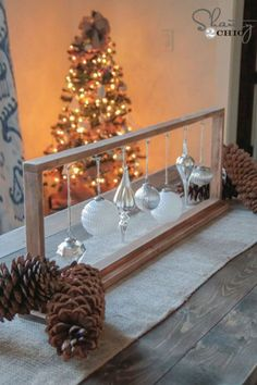 Christmas bulbs don't just belong on the tree: highlight some of your favorites on the dinner table with this elegant frame.  See more at Shanty 2 Chic. What you'll need: Silver ornaments ($10 for 24, amazon.com); Twine ($6, amazon.com); Cup hooks ($7, amazon.com)