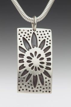 """Domed Rectangular Oxidized Sunflower Necklace. The necklace is made of sterling silver, domed, rectangular shapes which are 1"""" x 1/2"""" in dimension. They are pierced with a design of sunflowers and oxidized in the recesses of the designs to make the design stand out using contrast. The chain is also made of sterling silver."""