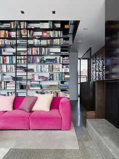 The books make a gorge backdrop for the pink sofa!