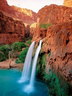 The twin streams of Havasu Falls splash down into a turquoise pool. The falls are located on the Havasupai Indian Reservation, which lies just outside Grand Canyon National Park.