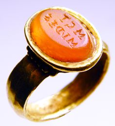 An ancient Roman gold finger ring set with a carnelian gem inscribed: M C T / M I ` D E S.