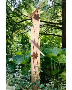 In diesem Wildgarten kommt das Standvogelhaus mit Nistkasten sehr gut zur Geltung. Das Grün der Tannenbäume, die Sträucher und Bodenpflanzen sorgen für einen gut gelungenen farblichen Kontrast zum naturbelassenem Massivholz dieser Gartenskulptur. Heimische Vögel wie Sperlinge, Kleiber,Gartenrotschwanz und Meisen bleiben durch die Höhe vor Katzen geschützt.