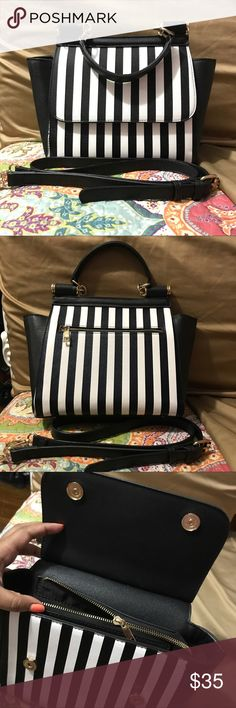 Black & white striped bag/ crossbody NWOT this is a structured bag/crossbody with gold hardware. Absolutely no flaws! It has been sitting in my closet in a bag for over a year, Ive never used it! It is made out of a sturdy material (stiff like saffiano leather, so it doesn't slouch, and keeps its shape beautifully). Has a interior and exterior back  zipper pocket and two other pockets inside. Also has little begs at the base so it won't get dirty if you set it down. Bags Crossbody Bags