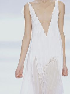 Long white pleated dress with staggered neckline; architectural fashion details // Akris