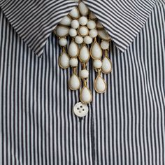 Waterfall brooches with suspended tassels look stylish worn centrally with a collar. Vintage brooch, signed Trifari, £35 from Otterley & Hester. http://otterleyandhester.co.uk/collections/brooches/products/trifari-white-vintage-brooch