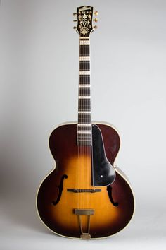 Vega Vegaphone C-75 Model Arch Top Acoustic Guitar, c. 1938, made in Boston, Mass., serial # 38615, sunburst lacquer finish, rosewood back and sides, spruce top; laminated mahogany neck with ebony fingerboard, original black hard shell case. This very finely built Vega archtops of the 1930's r...