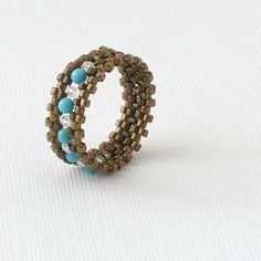 Beaded Ring - Use a combination of double-needle weave and peyote stitch to create sweet band rings with crystal, pearl or gemstone accents. As shown, these rings are approximately 8mm wide;