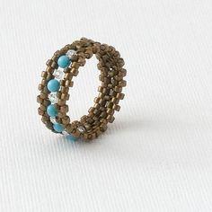 Tutoriels de bijoux Tales:... Lorsque vous voulez raconter votre propre histoire.    Utiliser une combinaison de double-aiguille tissent et peyote stitch pour créer des anneaux de bande douce avec cristal, perle ou accents de pierres précieuses. Comme indiqué, ces anneaux est environ 8mm de large ; elles peuvent être faites encore plus larges en ajoutant des lignes supplémentaires, si vous le souhaitez. Elles sont possibles pour sadapter à nimporte quel doigt de taille. Ce projet de tissage…