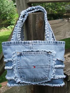 This is a small to medium size denim tote bag made mostly from repurposed Tommy Hilfiger brand jeans. The functional back pockets are on both