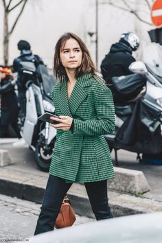 A green plaid, wide lapel jacket cinched at the waist back to denim