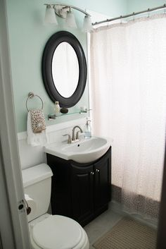 Small vanity and placement of towel ring, mirror and shelf. Also, note 3 lights above mirror