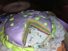 Detalle del corte de mi primera tarta de fondant. Bizcocho arcoiris con frosting de cheescake de vainilla. Marzo de 2012.