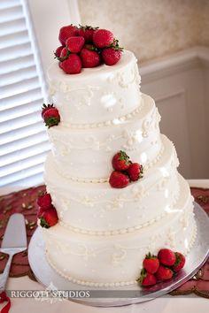Wedding cakes from various weddings in Minnesota by Rochester, Minnesota wedding photographer, Dean Riggott, of Riggott Studios. White with strawberries. Berries on white.  © Riggott Studios. http://www.riggottstudios.com