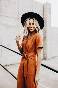 Burnt orange tied up jumpsuit/romper with a wide brim black hat. so chic and easy