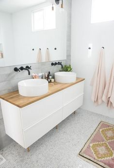 Wake up and glide into this feminine dream of a minimalist bathroom. The white marble sink bowls are like clouds floating in interior design heaven. The natural wood countertop adds an intriguing contrast to the dark iron faucet.  // #Bathroom #WoodWorkingProjects #CraftCakery #BathroomIdeas // Source: Minimalist Home UK