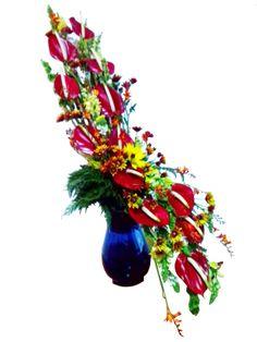 diseño floral estilo curva de Hogarth elaborado con anturios, molucella, snapdragon y diversos fillers