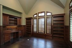TO THE LEFT OF THE 2-STORY ENTRY HALL, THE HANDSOME PRIVATE STUDY FEATURES A VAULT CEILING, WIDE-PLANK TIGERS EYE WALNUT FLOORS, LIBRARY SHELVES & CABINETS, PLANATATION SHUTTERS.
