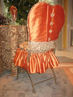 This is my Pumpkin Spice Chair Suit® made of pumpkin orange silk and muted autumn patterned tapestry.  The jacket has covered button closure and lower edge banding.  The skirt has a tapestry boxed cushion with gathered silk skirt and silk ties to connect to the chair.  Both the jacket and skirt are lined.    Each set is custom made to fit your chair.  Dry clean only. (This chair happens to be a shaped iron bistro chair.)