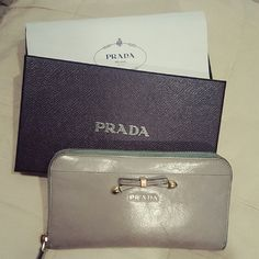 100% AUTHENTIC PRADA LEATHER CLUTCH WALLET All leather inside and out. Asia exclusive edition purchased in Japan 2 years ago. Have been using it for a year, normal wears shown include stretch on the leather, color transfer, light wrinkles and a few light fingernail scratches which is very common on genuine leather.  I used it as a clutch since it's big enough to hold all my cards/cash/Samsung 6s. 100% Authentic,  Box and Auth card are included Reasonable offer considered Prada Bags Wallets