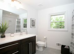 This totally renovated guest bathroom of a mid century modern home features custom espresso cabinetry with quartz countertop and Grohe fixture, tile floor and tub/shower surround and a modern vanity fixture.