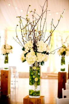 Natural wooden columns flanking the ceremony aisle, featuring centerpieces with sliced limes and white hydrangeas