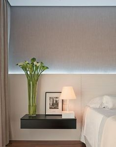 Quarto de casal pequeno. Soluções: cabeceira em MDF, branca, em toda a extensão da parede, com iluminação de LED indireta. Papel de parede em tom neutro.