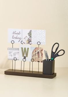 Do you, desk decor genius, take this walnut photo display as your favorite tabletop accessory? Of course you do! A marriage between modern design and fab functionality with its black keyrings for holding pics and memos, and a multi-purpose ceramic cup, this piece is one you'll love and cherish for all time.