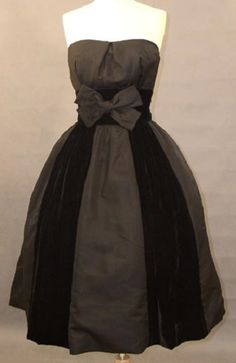 1950's strapless black faille and velvet cocktail party dress, with strapless fitted bodice in faille, set-in velvet waist with large faille bow, and a full skirt done in alternating panels of faille and velvet. by Hattie Carnegie.