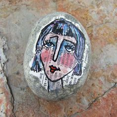 Face Rock 15: original painted lady face on smooth stone, gouache, ink, face on rock, decoupage, one of a kind, paperweight. $15.00, via Etsy.