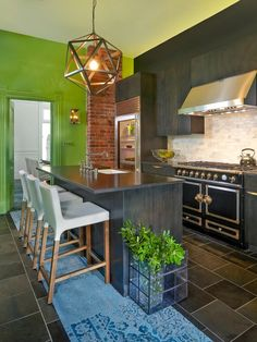 Beautifully designed kitchen with bright green wall and dark grey cabinets