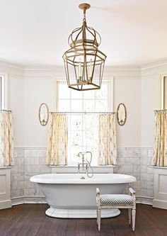 In this beige bathroom, a stone chair rail pairs perfectly with beige walls and window treatments. Dark hardwood flooring grounds a gold chandelier and mirrored sconces. Coordinating white on the bathtub and ceiling pulls eyes upward and around the beige walls and moldings. #bathroomideas #bathroomcolorschemes #beigebathrooms #bathroomdecor #remodel #bhg