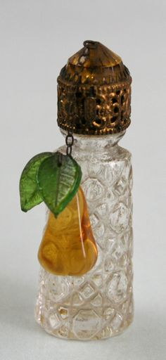 Vintage Mini IRICE Perfume Bottle  The bottle is a clear glass with a impressed design. It has one chain dangle with a glass pear and leaves. The dauber is present.