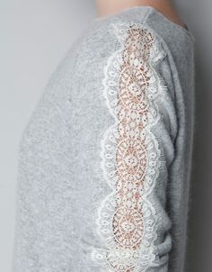 This shirt is from Zara, but could be an easy upcycle. To ensure the sweater retains it's shape, stitch the lace to the sleeve first, then cut away the underlying section of the sweater.