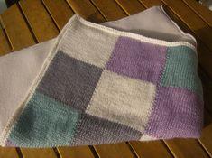 La couverture est composées de carrés de 25 mailles sur 30 rangs, le tout bordé sur les 4 côtés de point mousse. *Monter 100 mailles en écru, et tricoter 4 rangs de point mousse. *Au 5eme rang, commencer à tricoter les carrés: 25 mailles de chaque couleur, en prenant bien soin de croiser les fils derrière à chaque changement de couleur. *On tricote alors en suivant les couleurs sur 30 rangs, et au 31eme rang, on change à nouveau de couleur, et ainsi de suite, jusqu'à avoir 5 carrés en…