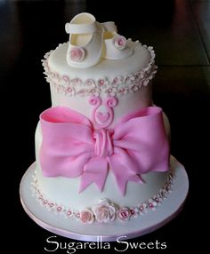 Beautiful 2 tier baby shower cake with baby shoe topper huge bow and sugar flowers. www.SugarellaSweets.com