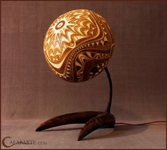 Fab CALABARTE Gourd lights.  Standing gourd lamp XII  Lamp is made of gourd brought from Senegal.  White carvings are deeper layer of white wood which allow some light to pass through it.  Perforation is made by drills in 10 different diameters.  The base is carved in wood and finished with italian natural oil.  On the underneath side of the base is burned Calabarte logo.  The middle part of the lamp is finished with black waxed string.  Its diameters are 20 and 22cm, and it is 39,5 cm high.