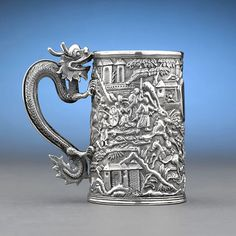 """This beautiful presentation silver tankard by Wang Hing of Hong Kong is a magnificent example of late 19th-century Chinese export silver. This double-skinned vessel features arepousséexterior of a battle executed in incredible detail. A dragon, the Chinese symbol of power and good fortune, serves as the handle of this fantastic tankard.    Marked """"WH""""    Circa 1890    4 1/2"""" wide (with handle) x 4 1/2"""" high"""