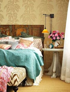 vintage rustic door as a headboard.  i love the colors on the bed and the wallpaper too!