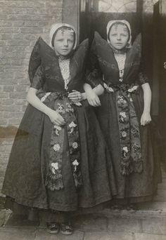 Twee meisjes in Axelse streekdracht. De meisjes zijn gekleed in zondagse dracht. Over de zwarte ondermuts en het oorijzer dragen ze een 'ronde muts' of 'hernhutter' (type muts), welke gedragen wordt tussen het 7e en 14e levensjaar. Aan de 'krullen' (oorijzeruiteinden) hangen 'dubbele strikken' (type oorijzerhangers). ca. 1942 #Axel