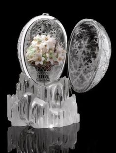"""The Winter Egg was designed by Alma Pihl, working for Peter Carl Fabergé. Tsar Nicholas II presented it as an Easter gift for his mother, Tsarina Maria Feodorovna. The rock crystal, moonstone & platinum egg is studded w/1,660 rose-cut diamonds. The miniature """"surprise"""" gold & platinum basket is also mounted w/1,378 diamonds & holds a bouquet of milk quartz flowers w/green garnet leaves. The price in 1913 was 24,700 rubles. It sold in 2002, for $ 9.6 million (US)."""