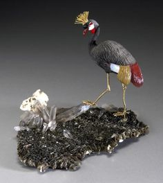 """Grey-Crowned Crane - Carved Russian obsidian, white and brown agate, coral, and red jasper. The eyes are citrine and onyx; comb and feet are gold-plated sterling silver. This bird is incorrectly labeled """"Mandarin Stork""""  on the website this is from."""