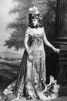 """The Honourable Mrs. Algernon Bourke (née Guendoline Sloane-Stanley) as Salammbo in serpent bangles and a """"drapery gown of white and silver gauze, covered with embroidery of lotus flowers,"""" for the Devonshire House Fancy Dress Ball, 2 July 1897"""
