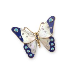 CARTIER. A LAPIS LAZULI, TURQUOISE AND MOTHER-OF-PEARL 'BUTTERFLY' BROOCH. Designed as a butterfly, each yellow gold wing set with carved mother-of-pearl accented with collet-set diamonds, the wing tips embellished with lapis sections accented with turquoise cabochons, the body set with two circular-cut sapphires, circa 1965, signed Cartier Paris French assay marks for gold and house maker's mark.