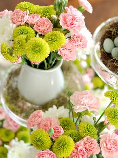 carnations and button mums. use red carnations with pink button mums and an olive green ribbon around the vase