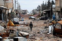 A man walks on a street of wrecked vehicles and buildings in the Syrian town of Kobani. The face of war.
