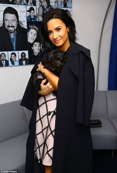 Cuddling: The raven-haired beauty got in a bit of a cuddle session with her four-legged friend before her interview with pal Nick