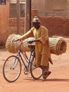 A man uses a bicycle to carry goods in Ouagadougou, Burkina Faso